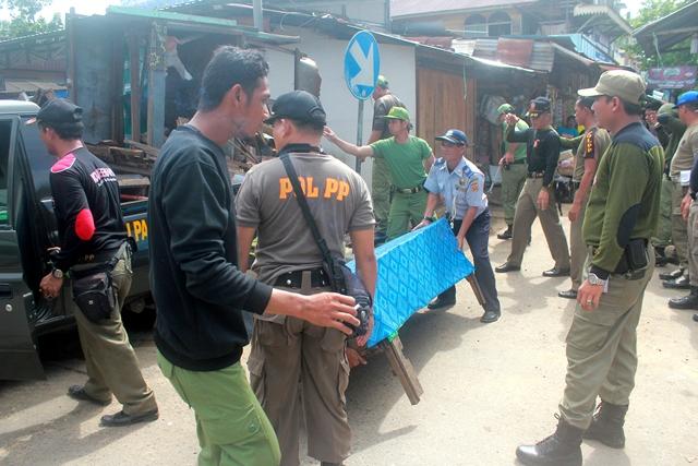 Saling bantu Satpol PP, Linmas dan Dishubkominfo mengangkat gerobak yang tidak terpakai di Pasar bauntung