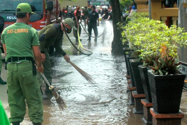 Pemadam Kebakaran menyemprot sisa sampah yang menyumbat selokan di pasar bauntung