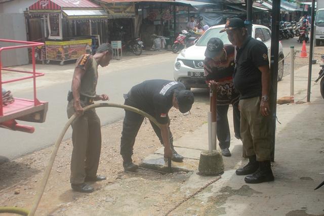 Kasatpol PP dan pemadam kebakaran menyemprot got yang buntu dari sela paving blok di Pasar bauntung